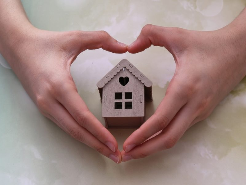 model house inside heart-shaped hands