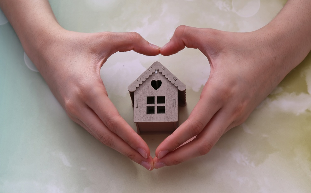 model house inside heart-shaped hands