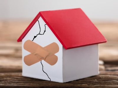 House with a band-aid across cracks