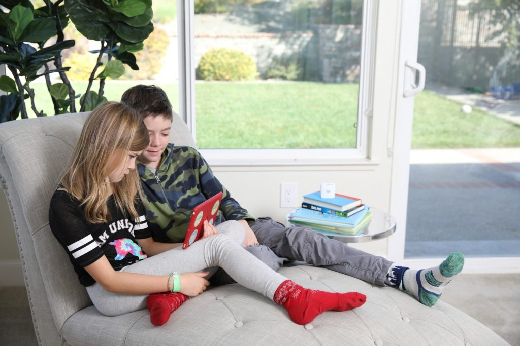 Two tweens on a couch sharing a tablet computer