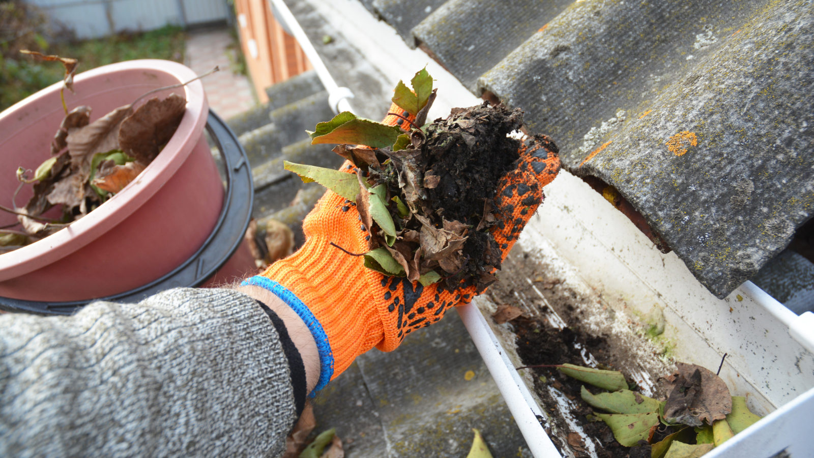 Man cleaning clogged gutter