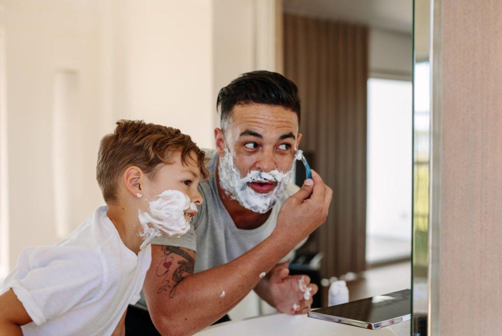 Dad and son in bathroom shaving