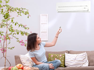 woman using remote control for air conditioner