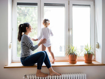 Mother sits on a window sill with child standing on hot water radiator