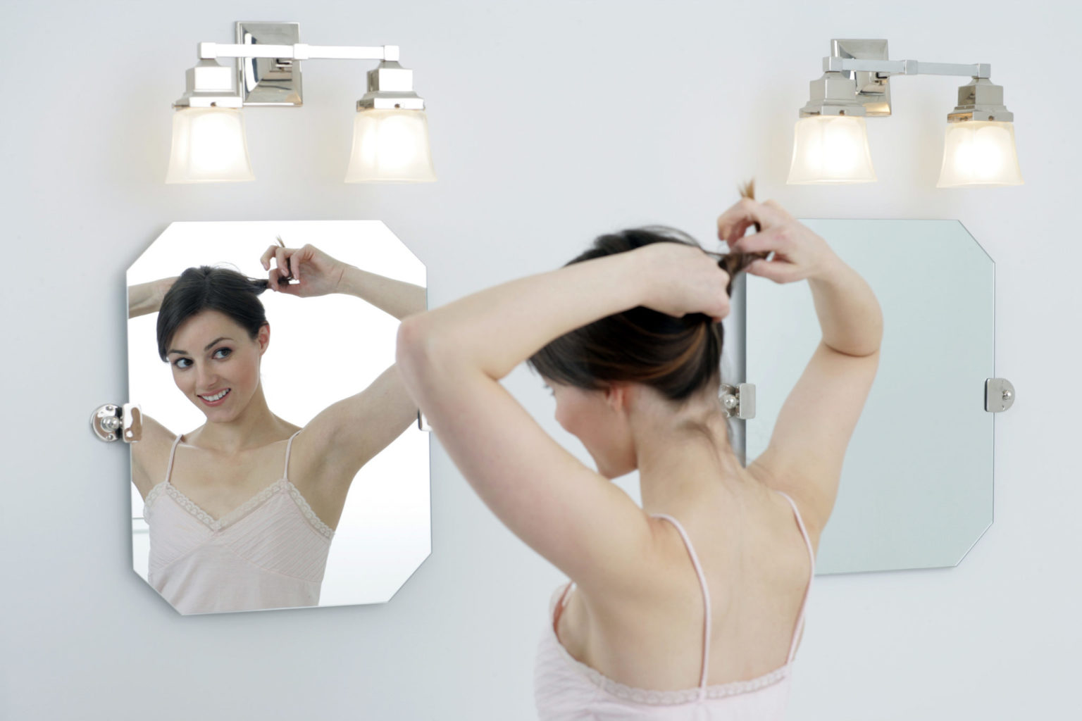 Bright bathroom with woman looking in mirror