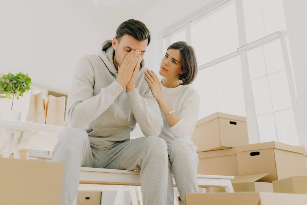 Husband and wife unhappy surrounded by moving boxes