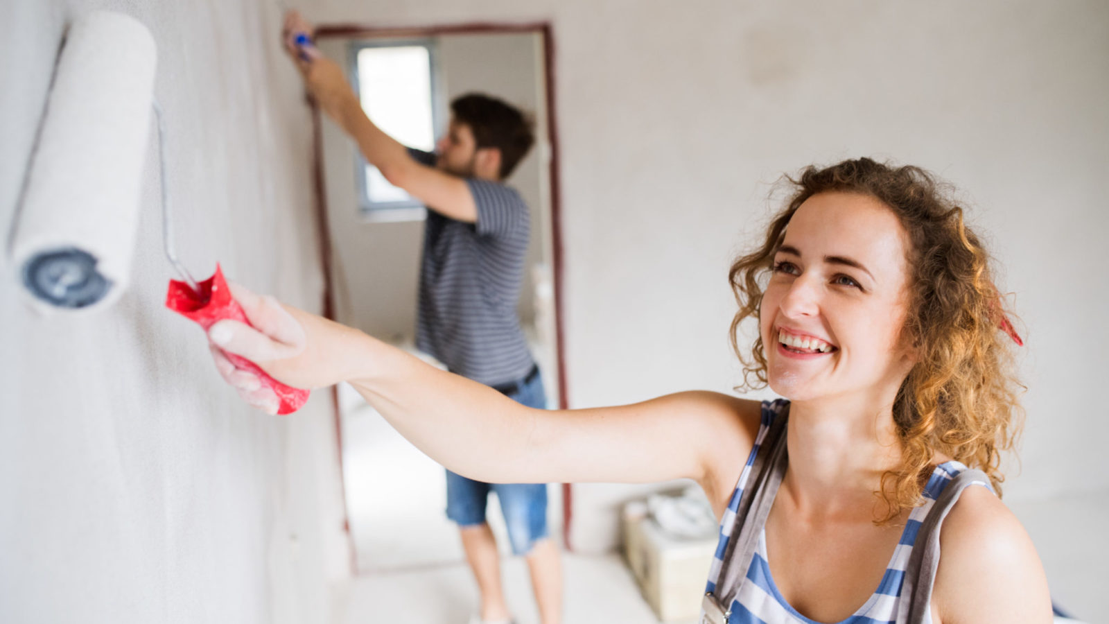 Young couple painting walls in their house