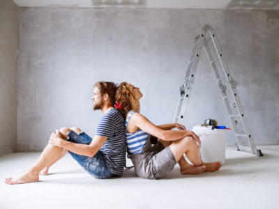 Millennial couple painting walls in their new house