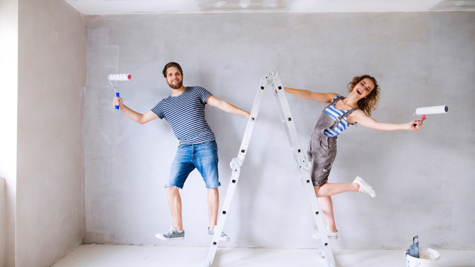 Couple on ladders painting walls