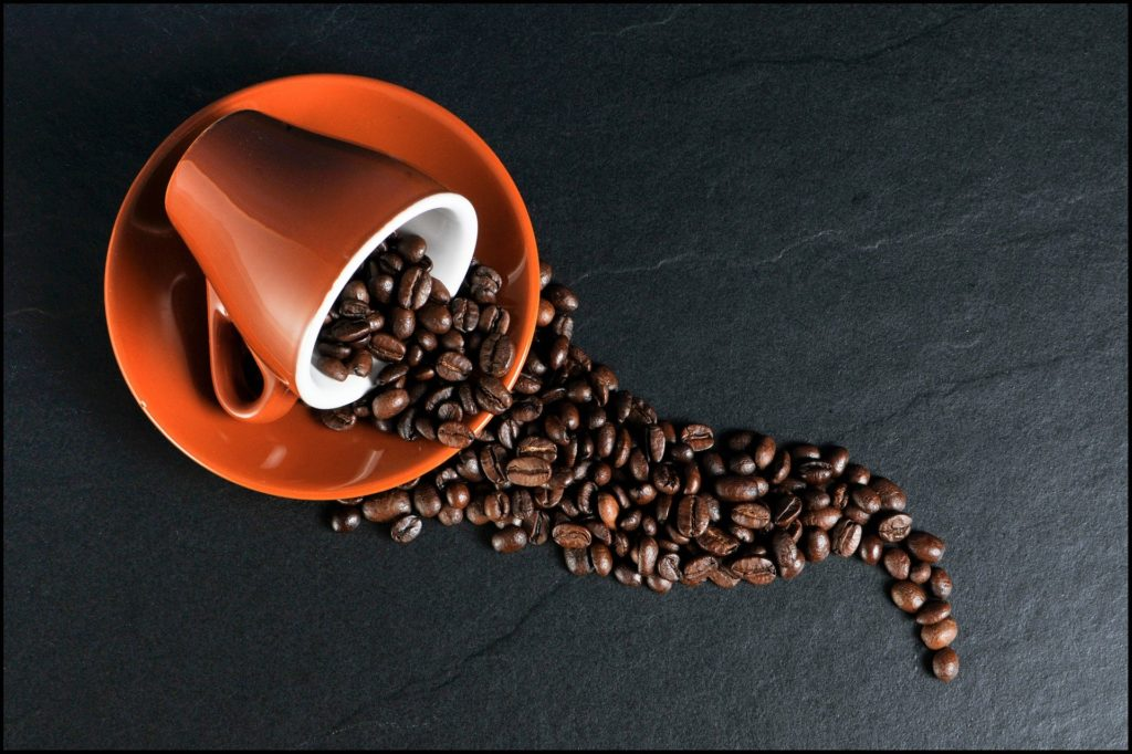 Coffee beans in orange ceramic mug