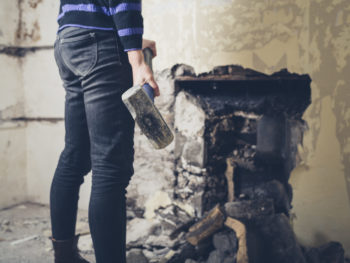 Woman destroying wall with sledgehammer