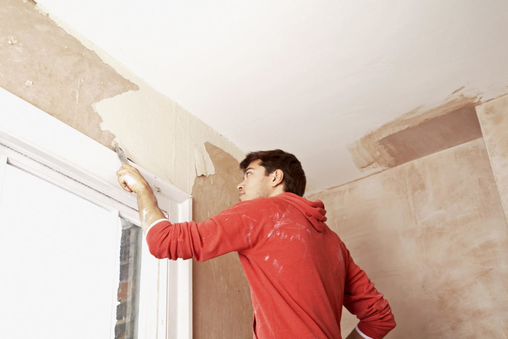 Man scraping paint off a wall