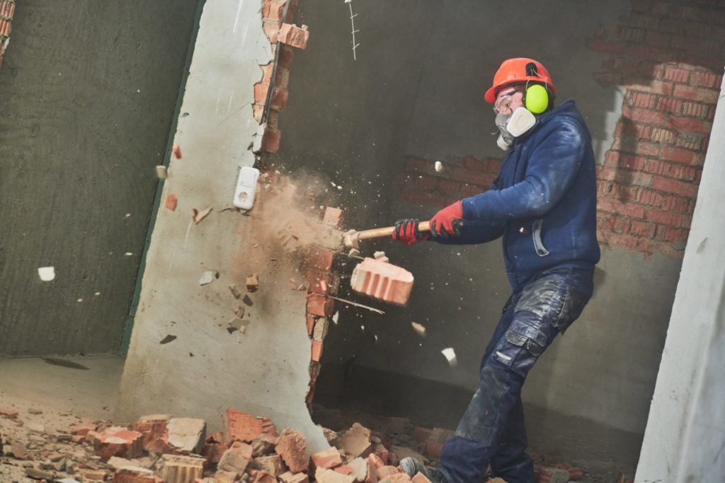 Man destroying wall with sledgehammer releasing toxic dust