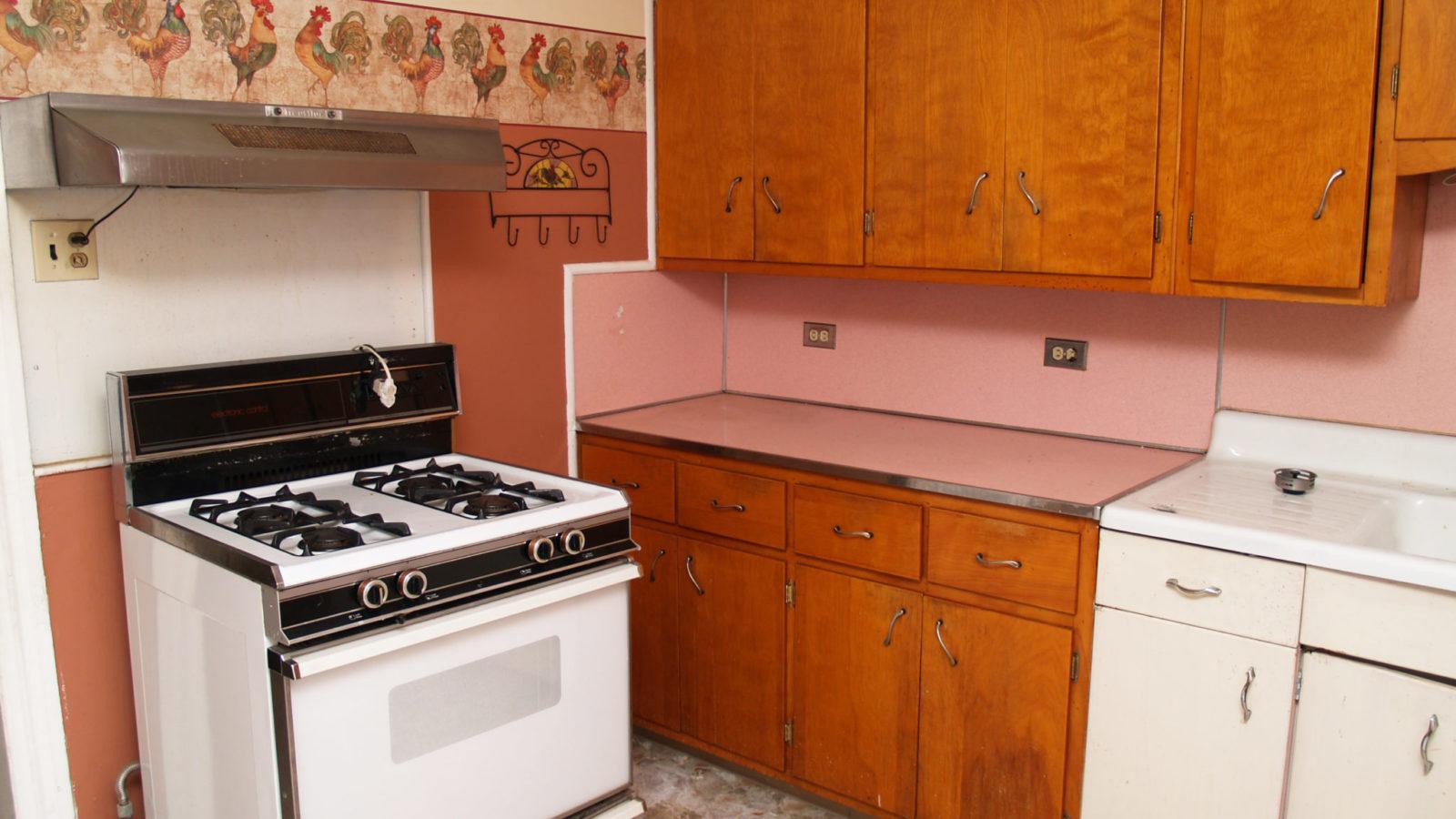 Old kitchen with pink backsplash and wallpaper border