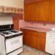 Old kitchen with pink backsplash and wallpaper border