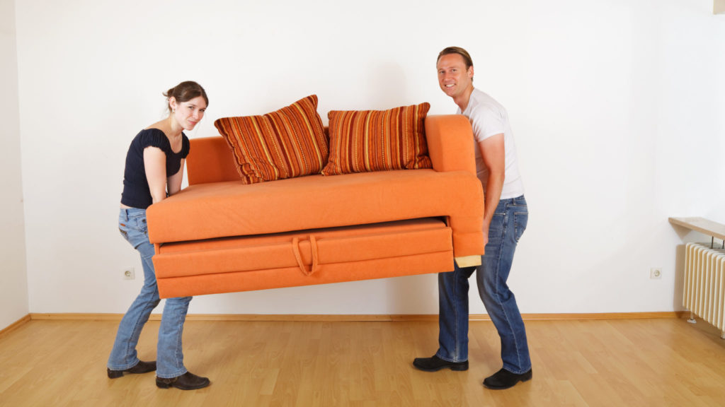 Young couple moving couch.