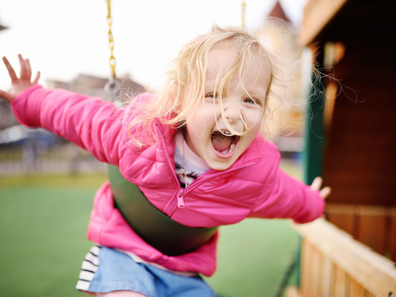 Child playing on backyard swings