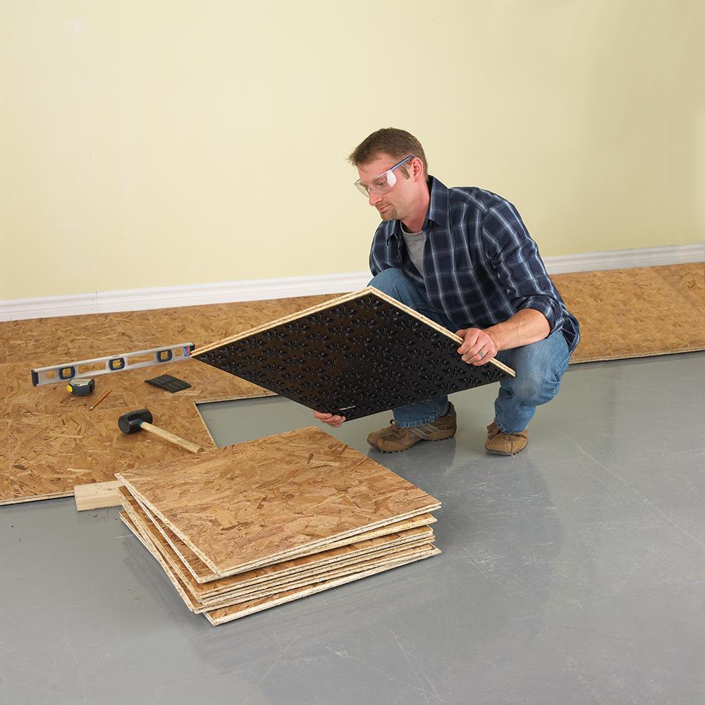 Man installing DRICORE basement flooring