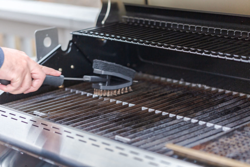 Man cleaning gas grill