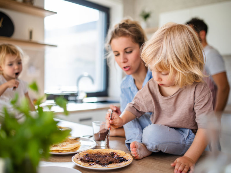 Young family with two small children indoors in kitchen, eating pancakes.
