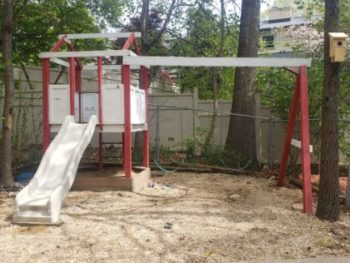 Plastic swing set on sandy soil