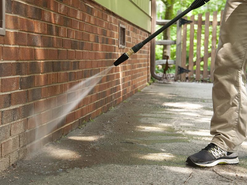 Man pressure washing siding