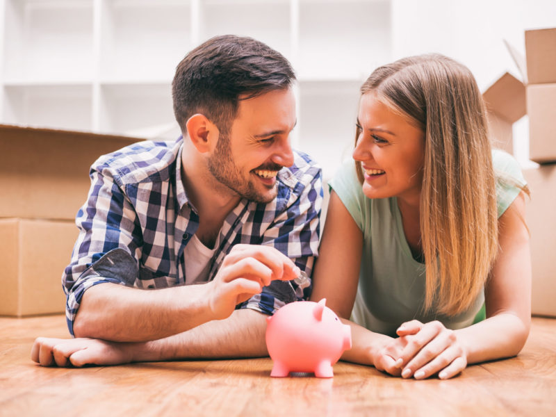 Young couple placing money in a piggy bank