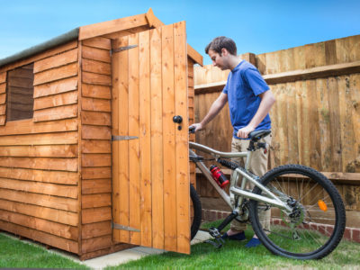 Man pushing his bike into a shed for storage