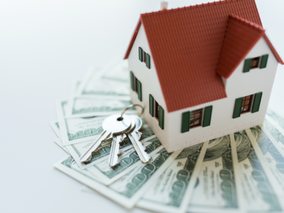 House and keys on top of money