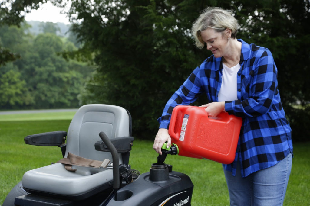Woman adding gas to a mower