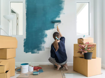Young woman painting interior wall