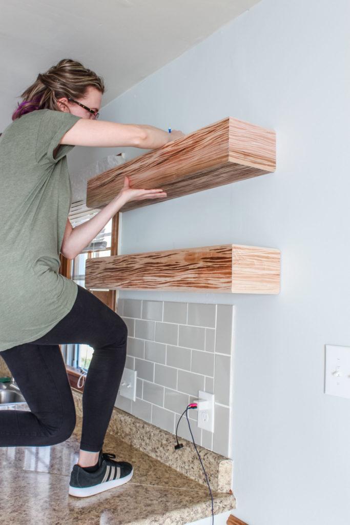 Woman installing a floating shelf
