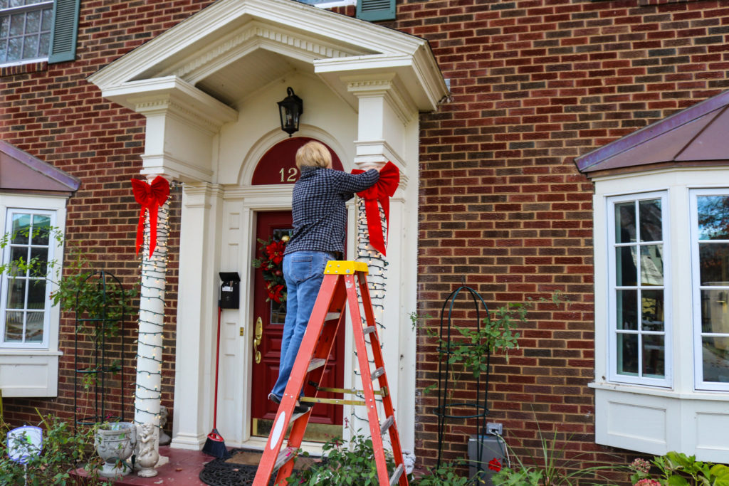 Woman on ladder putting Christmas decorations up