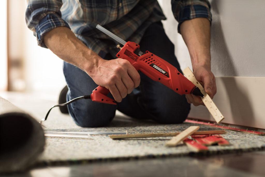 Man using Arrow GT300 Glue Gun on Carpet Repair