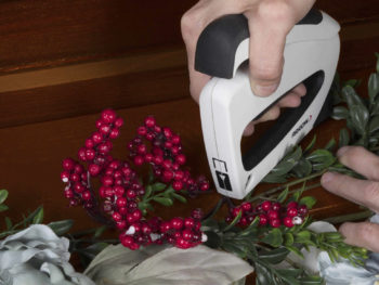 Woman using Arrow staple gun on a holiday decor project