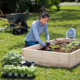 Woman planting in a raised garden bed