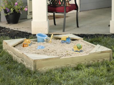 Sandbox with toys in a back yard.