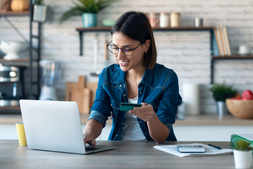 Woman holding white credit card for shopping in the kitchen at home.