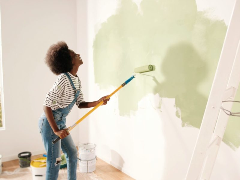 Young woman painting wall with roller