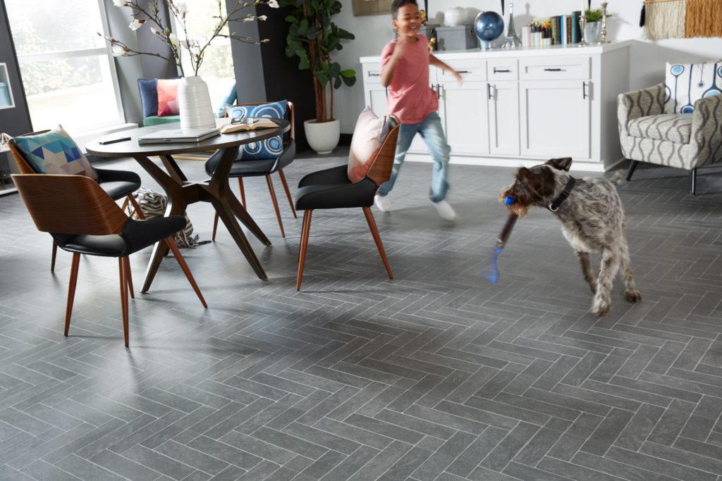 Child and dog playing on LL Flooring Burgess Gray AquaSeal Laminate Floor