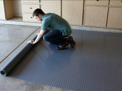 man rolling out garage floor mat.