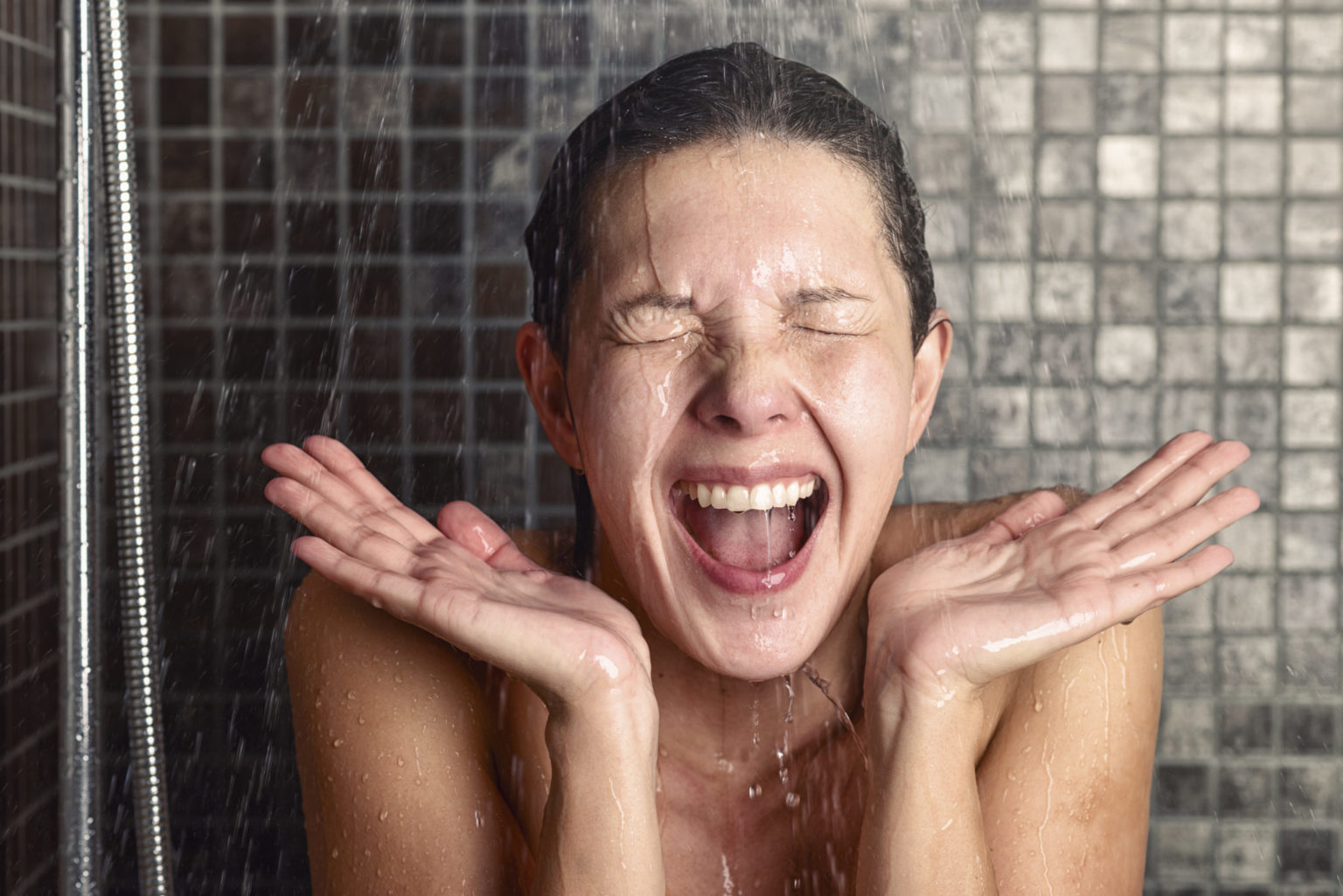 Young woman reacting in shock to hot or cold shower water as she stands under the shower head washing her hair eyes closed with her hands raised and mouth open