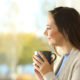 Woman holding coffee cup looks out through window on a cold day.
